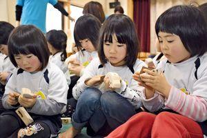 紙やすりを使って車体を磨く園児たち=佐賀市の北部保育園