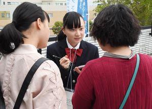 来場者にインタビューする白石高新聞部2年の安井典さん(右)=佐賀市文化会館