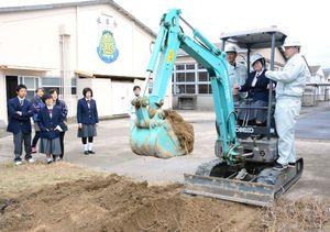 特別支援学校の生徒に寄り添って、ショベルカーの操作を教える唐津工業の生徒=唐津工業高