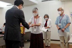 九州電力の担当者に玄海原発の稼働停止などを記した要請書を手渡す石丸初美さん(左から2人目)=福岡市の九州電力本店