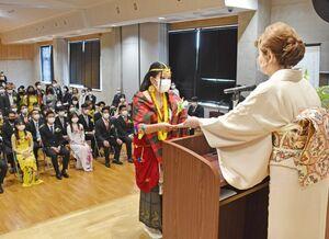 山本由子校長(右)から卒業証書を受け取る弘堂国際学園の生徒ら=鳥栖市のCODO外語観光専門学校