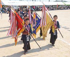 優勝旗や優勝カップを掲げながら堂々と行進する江北少年剣道クラブ=江北町の江北中グラウンド