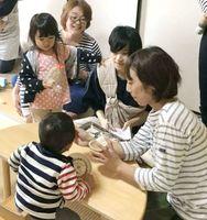 赤ちゃんに離乳食を食べさせる参加者(昨年12月)=佐賀市のポコ・ア・ボッコ