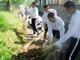 開校120周年を締めくくる清掃活動で、学校周辺の落ち葉などを拾い集める鹿島高校の生徒たち=鹿島市の同校周辺(提供写真)