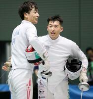 男子エペ準決勝で宇山賢(左)を破り、健闘をたたえ合う見延和靖=駒沢体育館