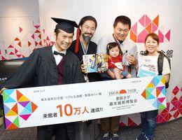 10万人目で来場した家族(右)を祝うセレモニー=佐賀市城内の幕末維新記念館