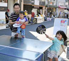 風呂桶のラケットのラケットで熱戦を繰り広げる参加者と武雄高校生=武雄市武雄町の温泉通り