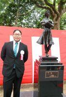 彫刻家諸井謙司さんとブロンズ像「こころは旅へ」=佐賀市の佐賀県立図書館