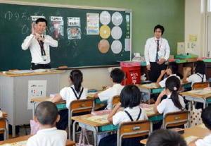 お金の大切さを子どもたちに伝えるゆうちょ銀行佐賀店の日高孝彰さん(左)と田代樹さん=佐賀市の南川副小学校