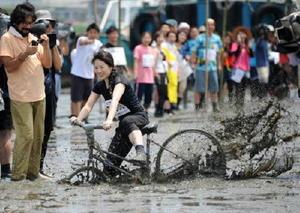 細い板を自転車で走る「ガタチャリ」。無事に渡り切れてもブレーキが無いので干潟に一直線