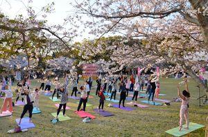 満開の桜の下、ヨガを楽しむ参加者=唐津市の鏡神社宮ノ原