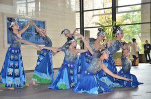 きらびやかな衣装をまとい、少数民族の歌や踊りを披露した貴州省の舞踊団=県庁
