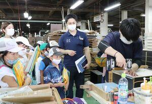 工場見学で職人から解説をうける児童ら=佐賀市諸富町の家具メーカー「レグナテック」