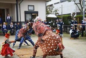 74年ぶりに里帰りした鉦(右奥)の音が響く中、奉納された獅子舞=鳥栖市藤木町の宝満神社下宮