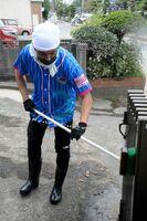 泥で汚れた家の門扉を洗浄するサガン・ドリームスの池田圭さん=武雄市北方町