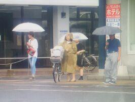 梅雨入りして雨が降り始めた佐賀市内。傘やレインコートを着て雨をしのぐ人々=26日午後、JR佐賀駅付近