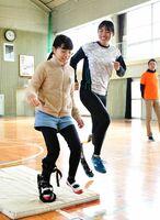 健常者用の義足を着け、山下選手(右)と一緒に駆け出す児童
