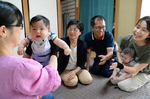 サポーターを実際に着けて、赤ちゃんをだっこする母親ら。中央が佐藤珠美佐賀大教授、右隣がイイダ靴下の佐竹裕介営業課長=佐賀市