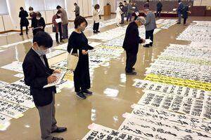 「第29回佐賀県書道展」の1次審査で、全国から寄せられた作品を採点する審査員=佐賀市の佐賀新聞社