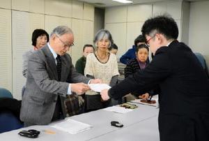 県民説明会の全20市町開催を求める要請書を県の担当者(右)に手渡す市民団体の代表者=佐賀県庁