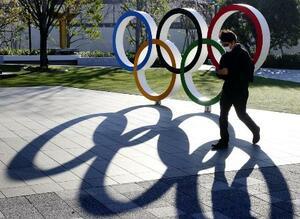 五輪マークのモニュメントの前をマスク姿で歩く人=24日午後、東京都新宿区