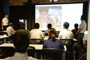 7月9日に開かれた第18期鳳雛塾のオープンセミナー。慶応大湘南キャンパスにいる飯盛理事長がネットを利用して講演した=佐賀市のオプティム・ヘッドクォータービル