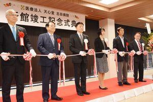 新館竣工記念式典が開かれ、テープカットする志田知之理事長(左から3番目)=鹿島市