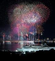 6000発の花火が唐津の夜空を彩った九州花火大会。右下はライトアップされた「ぱしふぃっくびいなす号」=唐津市の大島市民の森から多重露光撮影