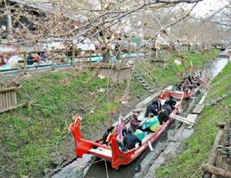 遣唐使船に乗り、水上から桜並木を観賞する参加者たち=佐賀市兵庫北のゆめタウン佐賀東側