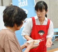 福岡県朝倉市の避難所で東北の郷土料理「はっと汁」の炊き出しを受け取る被災者(左)=10日