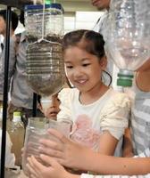 「わあすごい!」-ユニセフのブースで、汚い水をきれいにするペットボトルのろ過装置に喜ぶ子ども