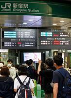 JR線の遅延を知らせる電光掲示板と、改札を通る利用客=20日午後6時42分、JR新宿駅