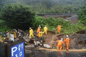 土砂崩れに巻き込まれた人がいないか、捜索する消防隊員=午後2時19分、唐津市厳木町の道の駅「厳木」