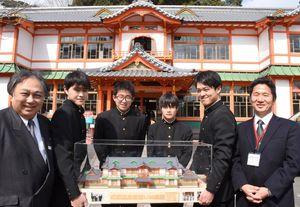 1年かけて制作した模型と(左から)田中社長、光武さん、江口さん、土井さん、宮本さん、津川久博塩田工高校長。後ろは武雄温泉新館
