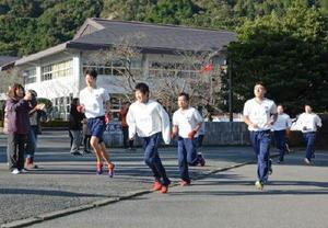保護者の声援を受けながら、30㌔走に挑む生徒たち=有田町の有田工高前