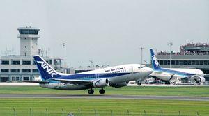 開港した佐賀空港で、送迎デッキから多くの人が見守る中、名古屋に向け離陸するANK機(手前)とエプロンに駐機する東京からのANA機=佐賀空港(1998年7月28日)