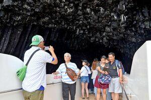 「イカ丸」のデッキスペースで、すぐ目の前に迫る七ツ釜を楽しむ観光客