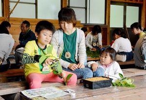 苗木づくりの体験で、植物の葉を切る親子連れ=佐賀市の県林業試験場