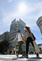 猛暑日となった名古屋市内を歩く人たち=10日午後