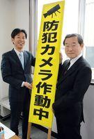 立て看板を手渡す県遊技業協同組合の新冨和紀理事長(左)と、県防犯協会の吉岡初彦専務理事=佐賀市の同組合