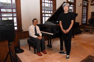 グランドピアノ設置を喜ぶ角田章裕店長(右)と調律師の西尾誠さん=佐賀市柳町の浪漫座