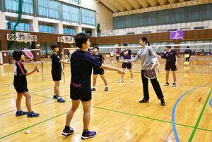 ラケットの持ち方をアドバイスする栗原文音さん(右)=佐賀市の旭学園体育館