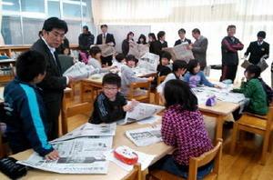 越地さん(左)の新聞ワークショップの様子。当日の紙面を教材に、新聞の秘密を語る=熊本県(提供)