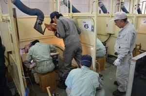 工業系高校の生徒たちが、県内企業の技能者からアドバイスを受けた溶接技術の講習会=佐賀市の県工業技術センター