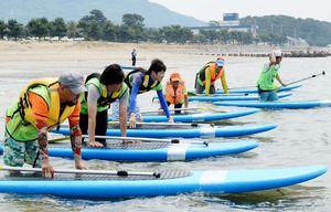 スタート位置に着く藤本拓希記者(左から3番目)=唐津市の浜崎海岸