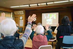 ビデオ会議アプリ「Zoom」でつながり、画面の向こう側に手を振る参加者ら=佐賀市の勧興公民館