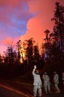 防じんマスクを装着して警戒に当たる州兵と、キラウエア火山から上がる噴煙=3日、米ハワイ島パホア(共同)