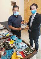サガン鳥栖の竹原稔社長(左)が、佐賀未来創造基金の山田健一郎代表理事に、歴代の記念ユニホームで作ったマスクを贈った=佐賀市唐人のまちなかオフィスTOJIN館