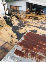 真っ黒な油が流れ込んだ民家の敷地内=杵島郡大町町(提供写真)