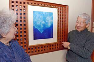 1998年、与那国島で撮影したジャック・マイヨールの写真を見ながら思い出を語る高島篤志さんと大河内はるみさん=唐津市東唐津の「洋々閣」